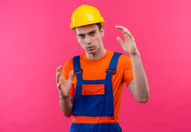 Młody konstruktor w mundurze konstrukcyjnym i kasku ochronnym pokazuje rozmiar rękami