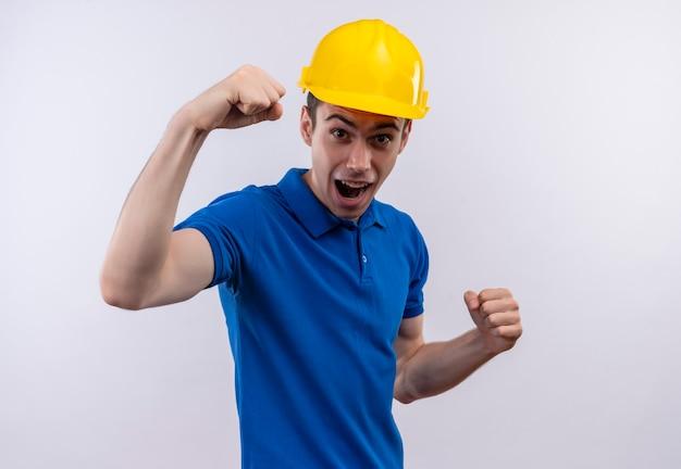 Młody konstruktor w mundurze konstrukcyjnym i kasku ochronnym robi radosną minę i podnosi pięści