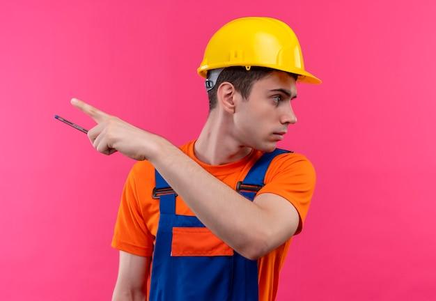 Młody konstruktor w mundurze konstrukcyjnym i kasku ochronnym trzyma pióro i wskazuje kciukiem w lewo
