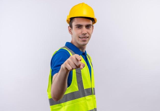 Młody konstruktor w mundurze konstrukcyjnym i kasku ochronnym uśmiecha się i wskazuje na ciebie palcem wskazującym