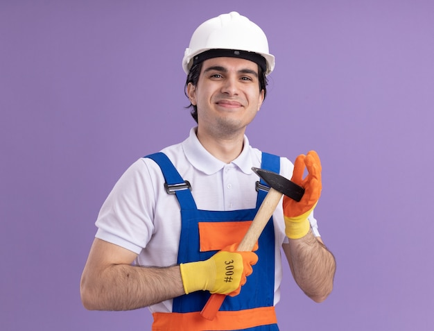 Młody konstruktor w mundurze konstrukcyjnym i kasku ochronnym w gumowych rękawiczkach trzymając młotek patrząc z przodu z uśmiechem na twarzy stojącej nad fioletową ścianą