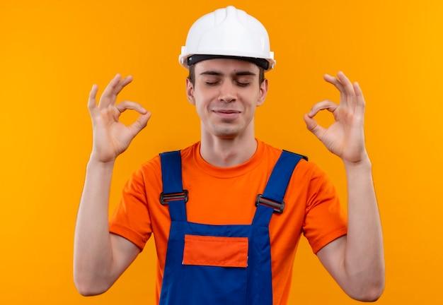 Młody konstruktor w mundurze konstrukcyjnym i kasku ochronnym, zamykając oczy i robiąc ok z rękami