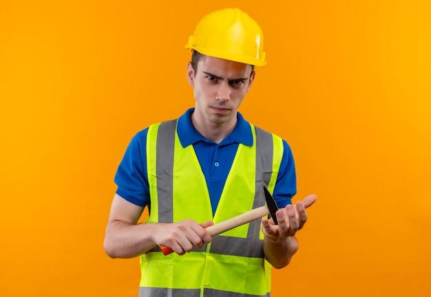 Młody konstruktor w mundurze konstrukcyjnym i kasku wygląda na złego i trzyma młotek
