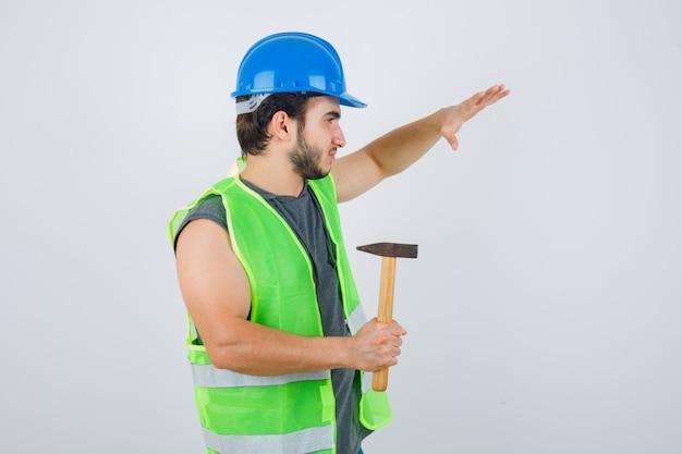 Młody konstruktor w mundurze odzieży roboczej podnosząc rękę, trzymając młotek i patrząc pewnie, z przodu.