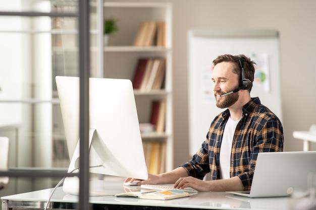 Młody konsultant dorywczo online komunikujący się z klientami w internecie, patrząc na ekran komputera w miejscu pracy