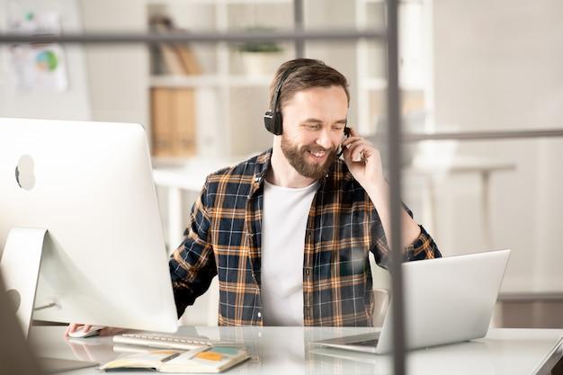Młody konsultant infolinii z zestawem słuchawkowym siedzi przed laptopem i komputerem i rozmawia z jednym z klientów online