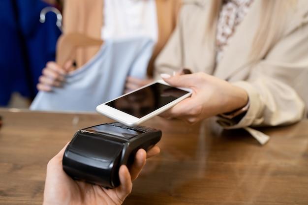 Młody konsument trzymający smartfon nad maszyną płatniczą trzymaną przez sprzedawcę podczas płacenia za zakup za pośrednictwem nfc