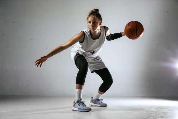 Młody koszykarz kaukaski żeński zespołu w akcji, ruch w biegu na białym tle na tle białej ściany. pojęcie sportu, ruchu, energii i dynamicznego, zdrowego stylu życia. trening, ćwiczenie.
