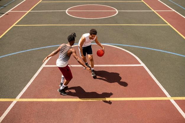Młody koszykarz próbuje bronić piłki przed rywalem, niosąc ją po boisku podczas gry