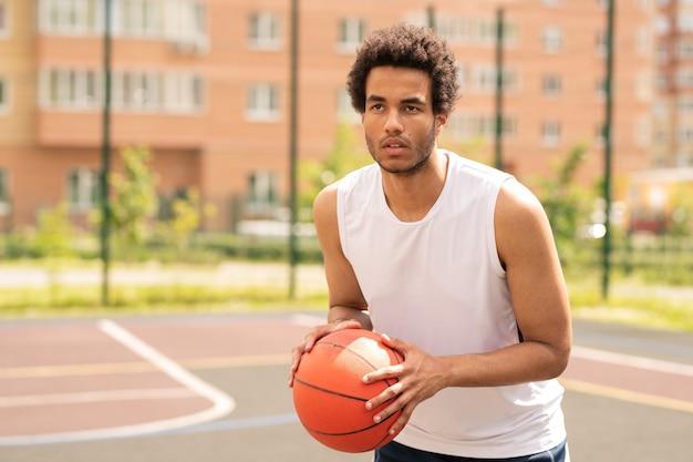 Młody koszykarz z piłką patrząc na kosz podczas gry na korcie lub placu zabaw