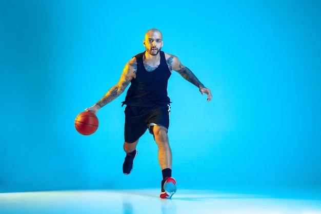 Młody koszykarz zespołu noszenia treningu sportowego, ćwiczenia w akcji, na białym tle na niebieskiej ścianie w świetle neonu