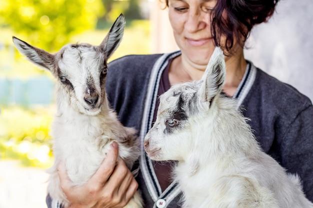 Młody kozioł na rękach kobiety. kobieta okazuje miłość do zwierząt domowych