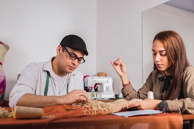 Młody krawiec i jego asystent przy pracy w warsztacie.