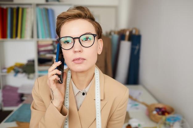 Młody krawiec w okularach rozmawia przez telefon komórkowy i porządkuje podczas pracy w warsztacie