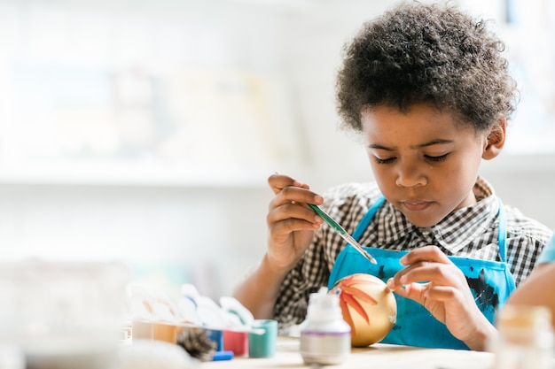 Młody kreatywny chłopiec z pędzlem maluje złotą piłkę zabawki boże narodzenie na lekcji podczas przygotowań do wakacji