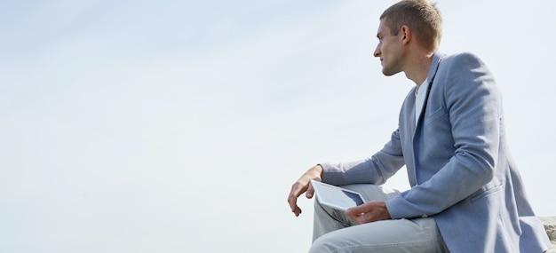 Młody kreatywny człowiek siedzi na naturze i przy użyciu komputera typu tablet.