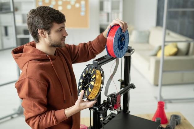 Młody kreatywny człowiek zmienia szpulę z filamentem stojąc przy drukarce 3d przed drukowaniem obiektów o różnych kolorach