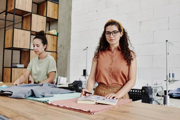 Młody kreatywny krawiec lub projektant mody w eleganckim ubraniu codziennym, patrząc na ciebie, stojącego przy stole z materiałem w warsztacie