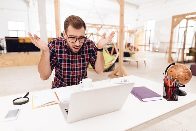 Młody kreatywny pracownik pracuje w jego biurze.