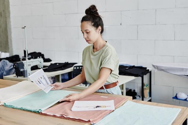 Młody kreatywny projektant mody, stojąc przy stole, poszukuje odpowiedniej tkaniny do nowej sezonowej kolekcji ubrań
