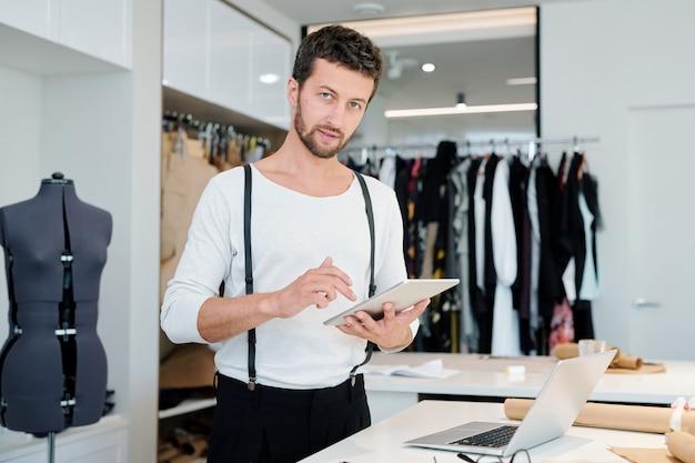 Młody kreatywny projektant mody z touchpadem patrzy na ciebie podczas przeglądania sieci w poszukiwaniu nowych modeli do kolekcji