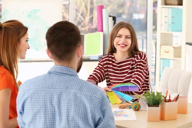 Młody kreatywny projektant pracujący z klientami w biurze