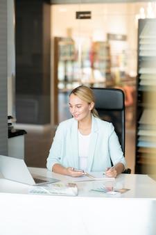Młody kreatywny projektant, siedząc w biurze, bierze udział w kursie wideo online poświęconym trendom w nowoczesnym designie