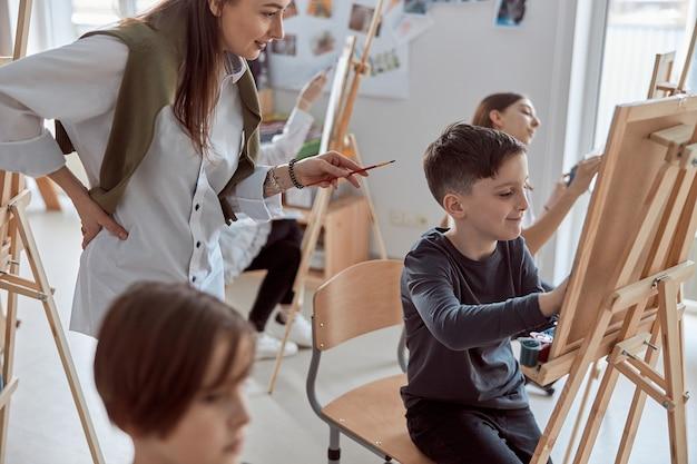 Młody kreatywny szczęśliwy chłopiec rysuje obrazek, podczas gdy nauczyciel mu pomaga