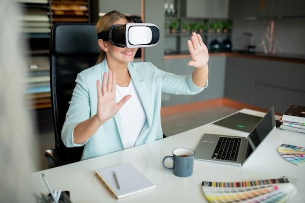 Młody kreatywny współczesny projektant oglądający wirtualny kurs i dotykający wyświetlacza siedząc w biurze