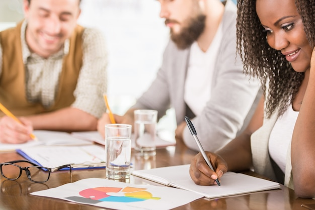 Młody kreatywny zespół burzy mózgów razem w biurze.
