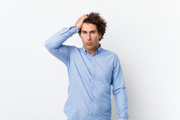 Młody kręcone dojrzały mężczyzna ubrany w elegancką koszulę zmęczony i bardzo senny trzymając rękę na głowie.