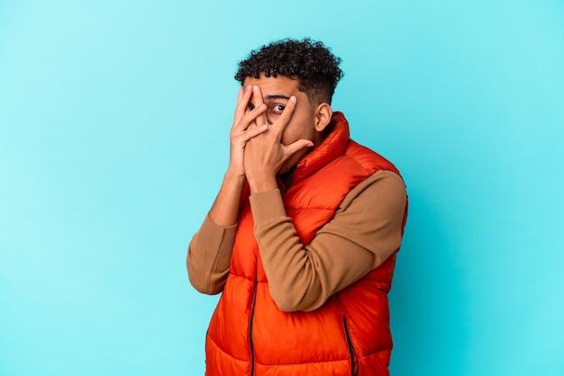 Młody, kręcony mężczyzna odizolowany na niebiesko mruga przez palce przestraszony i zdenerwowany