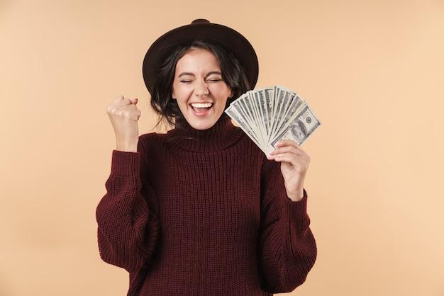 Młody krzyk emocjonalny brunetka kobieta na białym tle nad beżową ścianą trzymając pieniądze zrobić gest zwycięzcy.