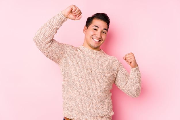 Młody krzywego mężczyzna pozuje w różowej ścianie odizolowywającej świętuje specjalnego dzień, skacze i podnosi ręki z energią.