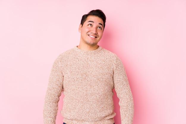 Młody krzywego mężczyzna pozuje w różowej ścianie odizolowywał marzyć osiągnięcie cele i zamierzenia