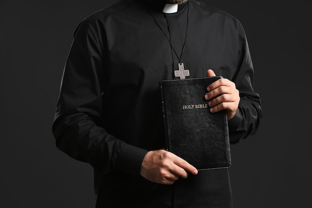 Młody ksiądz z biblią na ciemnym tle