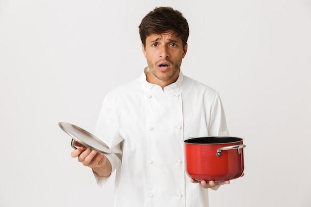 Młody kucharz człowiek stojący na białym tle na białej ścianie gospodarstwa naczynia.