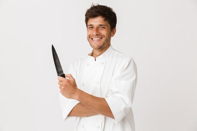Młody kucharz człowiek stojący na białym tle na białej ścianie trzymając nóż.