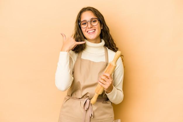Młody kucharz kaukaski kobieta na białym tle pokazano gest rozmowy telefonicznej z palcami.