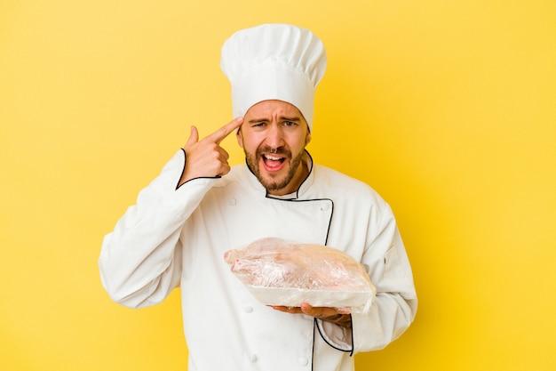 Młody kucharz kaukaski mężczyzna trzyma kurczaka na białym tle na żółtej ścianie, pokazując gest rozczarowania palcem wskazującym.