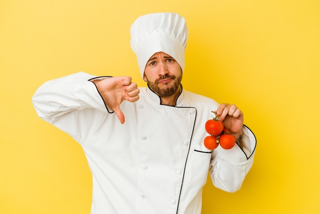 Młody kucharz kaukaski mężczyzna trzyma pomidory na białym tle na żółtym tle, pokazując gest niechęci, kciuk w dół. pojęcie sporu.