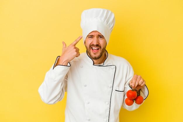Młody kucharz kaukaski mężczyzna trzyma pomidory na białym tle na żółtym tle, pokazując gest rozczarowania palcem wskazującym.