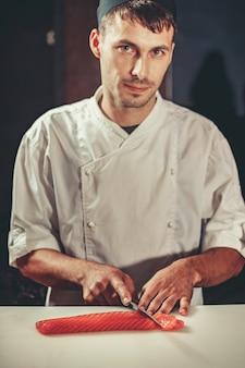 Młody kucharz kucharz ubrany w biały mundur cięte ryby łososia na stole w restauracji. pracuje nad sashimi. przygotowanie tradycyjnego japońskiego sushi we wnętrzu nowoczesnej profesjonalnej kuchni
