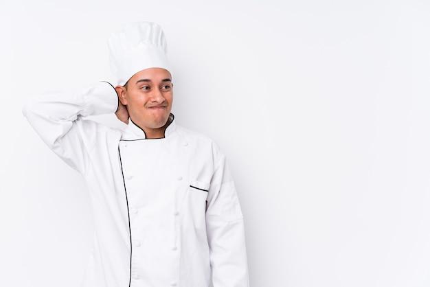 Młody kucharz łaciński mężczyzna na białym tle dotykając tyłu głowy, myśląc i dokonując wyboru.