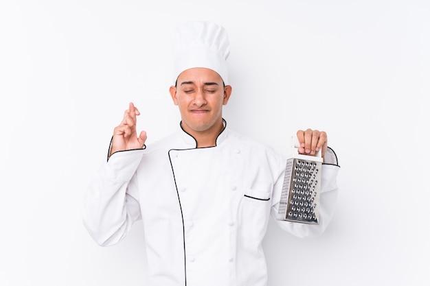 Młody kucharz łaciński mężczyzna na białym tle skrzyżowane palce na szczęście
