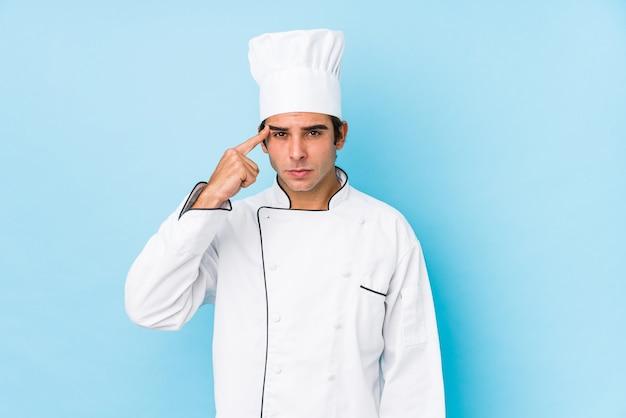 Młody kucharz mężczyzna na białym tle pokazano gest rozczarowania z palcem wskazującym.