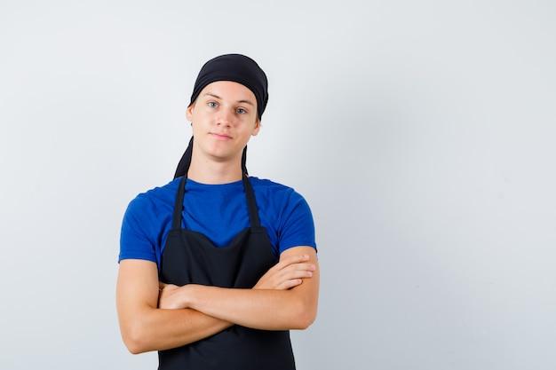 Młody kucharz mężczyzna stojący ze skrzyżowanymi rękami w t-shirt, fartuch i wyglądający pewnie. przedni widok.