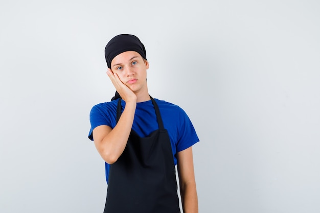 Młody kucharz mężczyzna w t-shirt, fartuch opierając policzek pod ręką i patrząc zamyślony, widok z przodu.