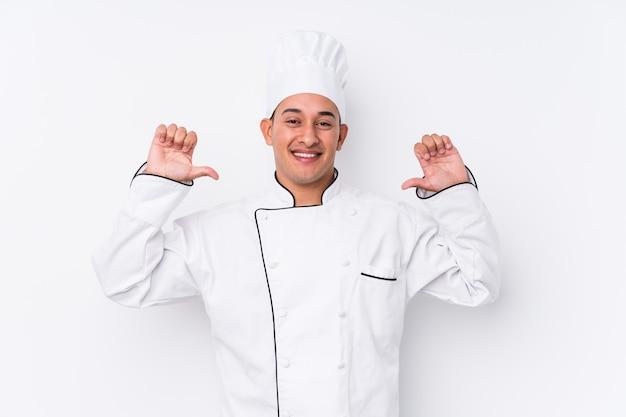 Młody kucharz na białym tle czuje się dumny i pewny siebie, przykład do naśladowania