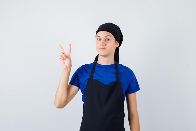 Młody kucharz nastolatek w t-shirt, fartuch pokazujący znak v i dumny, widok z przodu.
